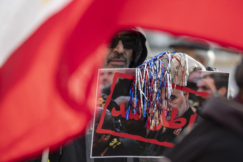 Supporters of the Mujahedeen-e-Khalq, or the MEK, an Iranian exile group, hold signs and flags during a show of support for a U.S. airstrike in Iraq that killed Iranian Gen. Qassem Soleimani, in Lafayette Park across from the White House, Sunday, Jan. 5, 2020, in Washington. (AP Photo/Alex Brandon)