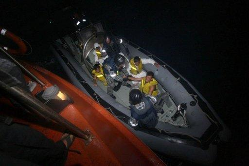 Australian navy personel transfer asylum-seekers to a Indonesian rescue boat near Panaitan island, West Java after the refugee boat sank. Afghans were among the 54 survivors from an asylum-seeker boat that disappeared two days ago off the Indonesian coast, but hopes of finding about 100 more missing were fading fast