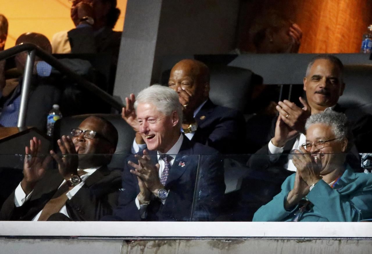 Former U.S. President Bill Clinton reacts to the speech by first lady Michelle Obama as former Attorney General Eric Holder (R, rear) and Representative John Lewis (D-GA), (rear) applaud at the Democratic National Convention in Philadelphia, Pennsylvania, U.S. July 25, 2016. REUTERS/Lucy Nicholson