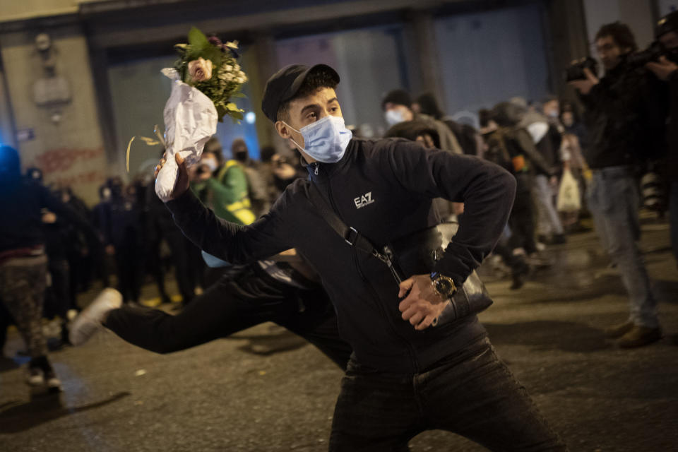 A man throws a bouquet of flowers against a national police station during a protest condemning the arrest of rap singer Pablo Hasel in Barcelona, Spain, Monday, Feb. 22, 2021. The imprisonment of Pablo Hasel for inciting terrorism and refusing to pay a fine after having insulted the country's monarch has triggered a social debate and street protests. (AP Photo/Emilio Morenatti)