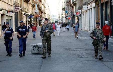 Police and army patrol the streets during the manhunt of a suspected suitcase bomber in central Lyon