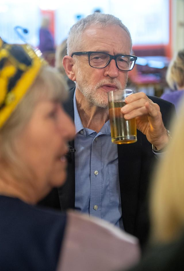 Jeremy Corbyn drinks an energy drink as he speaks with a group of WASPI (Women against state pension inequality) supporters during a visit to the Renishaw Miners Welfare, in Renishaw, Sheffield (PA)