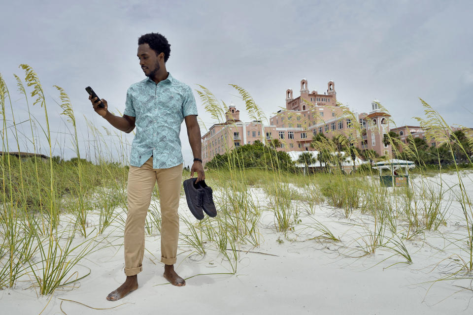"""Jared Wofford poses for photos outside of the Don Cesar hotel Thursday, June 17, 2021, in St. Petersburg, Fla. Wofford appears in the Amazon series """"Life's Rewards,"""" an original, scripted TV series commissioned by travel marketers in St. Petersburg and Clearwater, Florida, seeking to draw quarantine-weary tourists to the area's sugar sand beaches. (AP Photo/Chris O'Meara)"""