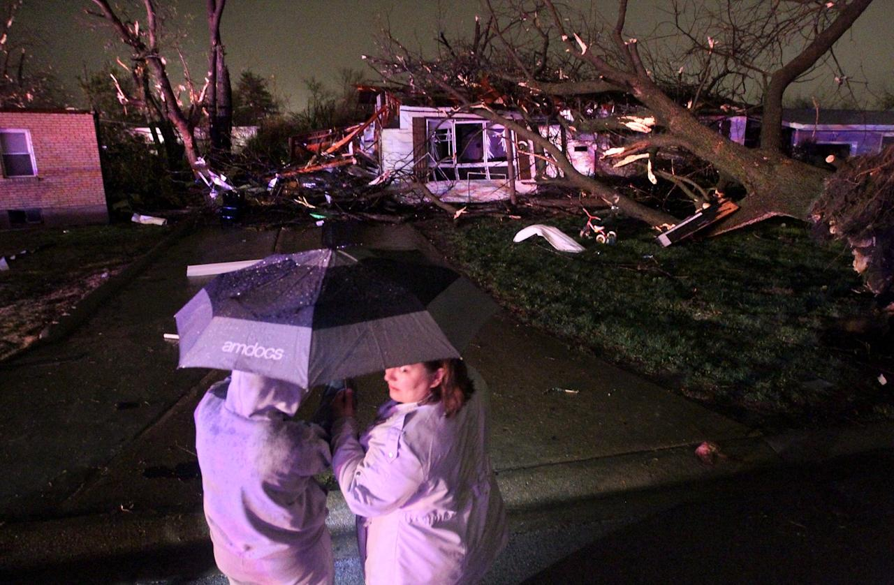 """Aimee Greenwalt (left) and Amanda Parish survey the damage in Hazelwood caused by a storm on Wednesday, April 10, 2013. Butch Dye, a hydrometeorological technician with the National Weather Service in St. Louis, Mo., said severe weather struck the suburb of Hazelwood. """"We won't be able to confirm whether it was a tornado until teams get out there tomorrow,"""" Dye said. (AP Photo/David Carson, Post-Dispatch)"""