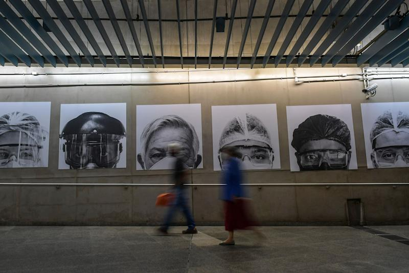 A couple walks past photos of medical workers by Brazilian photographer Thiago Santos at a subway station, in Sao Paulo, Brazil, July 29, 2020, amid the COVID-19 pandemic. (Photo by NELSON ALMEIDA / AFP) (Photo by NELSON ALMEIDA/AFP via Getty Images)