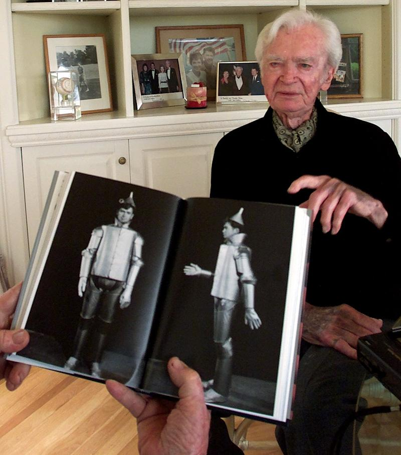 "Actor Buddy Ebsen, 93, points to a book that shows him wearing the costume of the Wizard of Oz' Tin Man, during an interview at his home in Palos Verdes Estates, Calif., May 24, 2001. Ebsen and his sister Vilma danced in hit Broadway shows, including ""The Ziegfeld Follies of 1934."" In 2001, Ebsen started a new career in fiction writing. His novel ""Kelly's Quest,"" released by an e-book publisher based in Indiana, became a best seller. (AP Photo/Damian Dovarganes)"