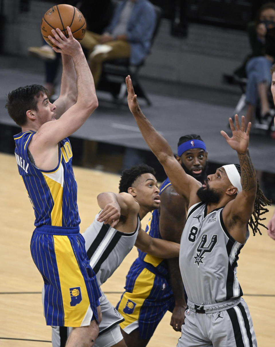 Indiana Pacers' T.J. McConnell, left, shoots against San Antonio Spurs' Patty Mills (8) as Spurs guard Keldon Johnson, second from left, and Pacers forward JaKarr Sampson watch during the second half of an NBA basketball game Saturday, April 3, 2021, in San Antonio. (AP Photo/Darren Abate)