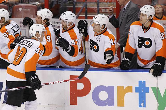Philadelphia Flyers center Vincent Lecavalier (40) celebrates with teammates after scoring a goal during the second period of an NHL hockey game in Sunrise, Fla., on Tuesday, April 8, 2014. (AP Photo/Terry Renna)