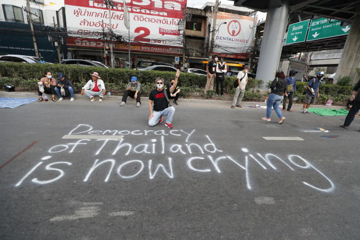 An anti-government protester flashes the three finger protest gesture while kneeling behind a slogan written on the road during a rally Wednesday, Dec. 2, 2020, in Bangkok, Thailand. Thailand's highest court Wednesday acquitted Prime Minister Prayuth Chan-ocha of breaching ethics clauses in the country's constitution, allowing him to stay in his job. (AP Photo/Sakchai Lalit)