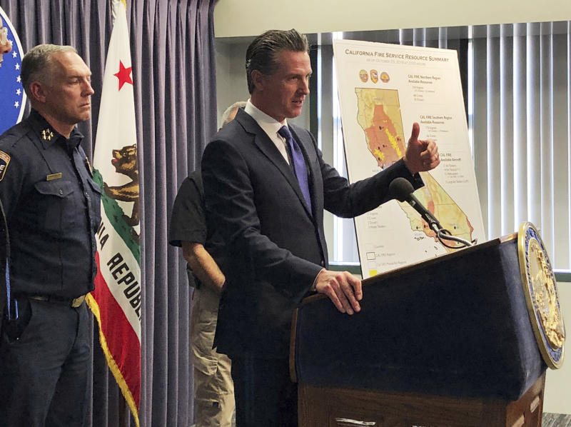 FILE - In this Thursday, Oct. 24, 2019, file photo, California Gov. Gavin Newsom talks with reporters as hundreds of thousands of Californians are again in the dark amid high wildfire danger in Los Angeles. Pacific Gas and Electric is promising on Friday, Jan. 31, 2020, to overhaul its board of directors in an attempt to avoid a potential takeover attempt by the state of California and prove the beleaguered utility is turning over a new leaf as it works through its second bankruptcy in less than 20 years. PG&E still must win over Newsom, who wants the company to replace its entire 14-member board. (AP Photo/Brian Melley, File)