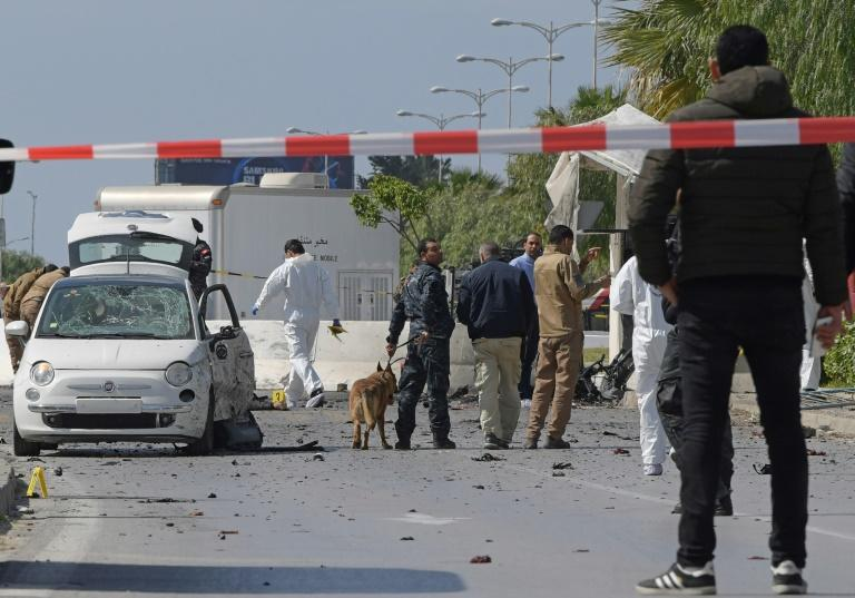 Police and forensic experts gather at the scene of a double suicide attack that targeted police near the heavily-fortified US embassy in the Tunisian capital