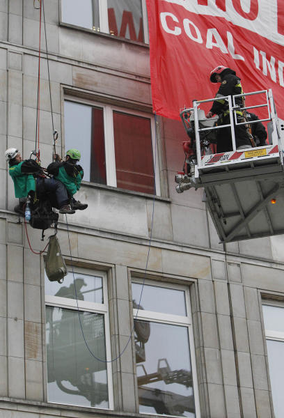 Police officers on the top of a fire ladder try to bring down climate activists who have gotten on the rootop of the Economy Ministry in Warsaw, Poland Monday, Nov. 18, 2013. Activists went up to the ministry rooftop to protest a coal conference opening to coincide with U.N. talks on preventing global warming, that is also the result of greenhouse gases coming from burning coal. (AP Photo/Czarek Sokolowski)