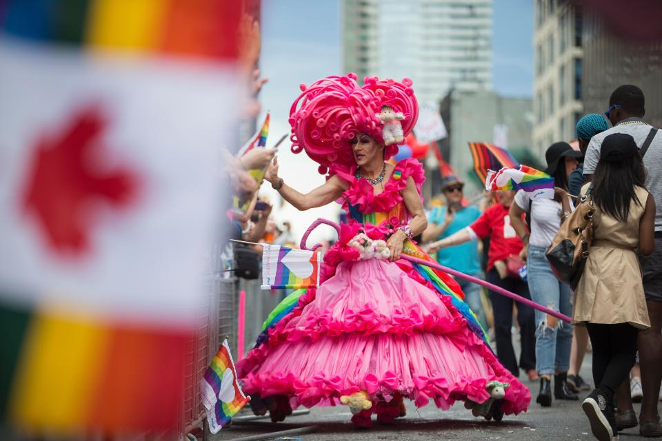 A drag queen high five's spectators during the Pride Parade in Toronto, Ontario, June 25, 2017. The event draws hundreds of thousands of spectators every year. / AFP PHOTO / GEOFF ROBINS        (Photo credit should read GEOFF ROBINS/AFP via Getty Images)