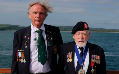 Les Budding, on the rights, tands with Philip Collins, 62, who is the son of the late F.E. Collins of 45 Commando, who fought alongside Budding on D-Day - Credit: AP Photo/Ben Jary