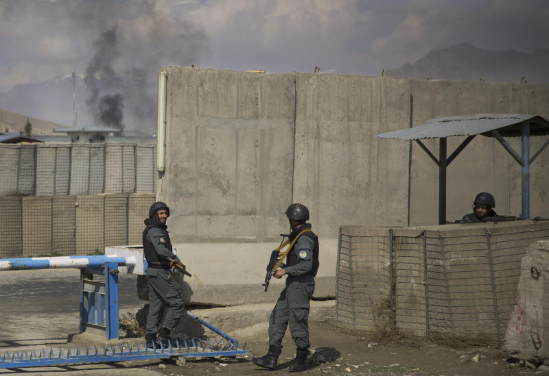 Afghan policemen take position while smoke from a burning building billows in the background as Taliban militants attacked the main Afghan election commission's headquarters in the outskirts of Kabul, Afghanistan, firing on the compound with rocket-propelled grenades and heavy machine guns from a house outside its perimeter wall, Saturday, March 29, 2014. Dozens of employees and other people who had been inside the Independent Election Commission compound took cover in the basement, and no casualties were reported. But two warehouses were hit and set on fire, witnesses said. (AP Photo/Anja Niedringhaus)