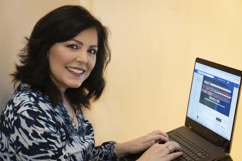 In this June 7, 2020, photo provided by Norm Tabije, Angela Keen uses her home computer in Honolulu to do work for her Facebook group, Hawaii Quarantine Kapu Breakers. The group, using the Hawaiian word for laws or rules, focuses on tracking down people who violate Hawaii's 14-day quarantine on travelers arriving to the state. (Norm Tabije via AP)