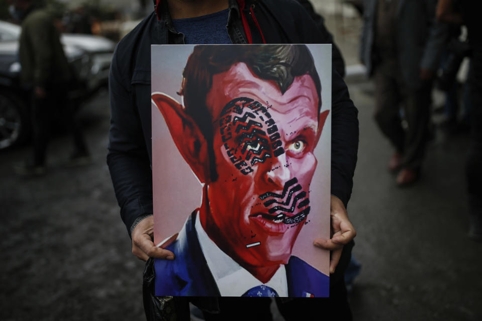 "FILE - In this Oct.30, 2020 file photo, a man holds a poster with a caricature of France's President Emmanuel Macron, depicting him as devil during a protest against France in Istanbul. A spotlight of suspicion encircled Muslims again even before the latest acts of extremist violence, including two beheadings. French President Emmanuel Macron has forged ahead with a plan to rid Islam in France of extremists, part a project he labels ""separatism,"" a term that makes some Muslims wince. (AP Photo/Emrah Gurel, File)"