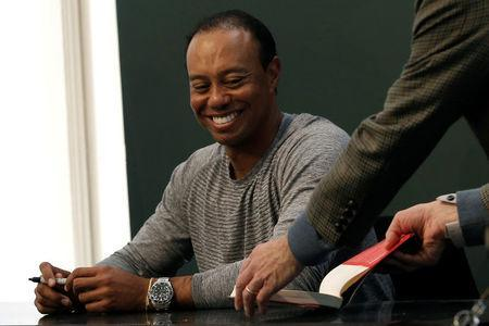 """Golfer Tiger Woods sits down to sign copies of his new book """"The 1997 Masters: My Story"""" at a book signing event at a Barnes & Noble store in New York City, New York, U.S., March 20, 2017. REUTERS/Mike Segar"""