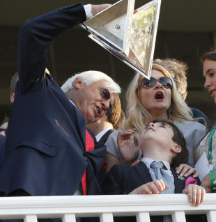 Bob Baffert holds up the Triple Crown Trophy with his son, Bode, and wife Jill. (AP)