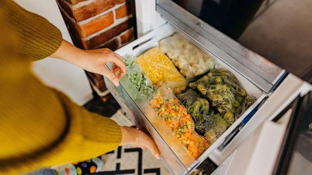 PHOTO: Woman putting container with frozen mixed vegetables to refrigerator (STOCK PHOTO/Getty Images)