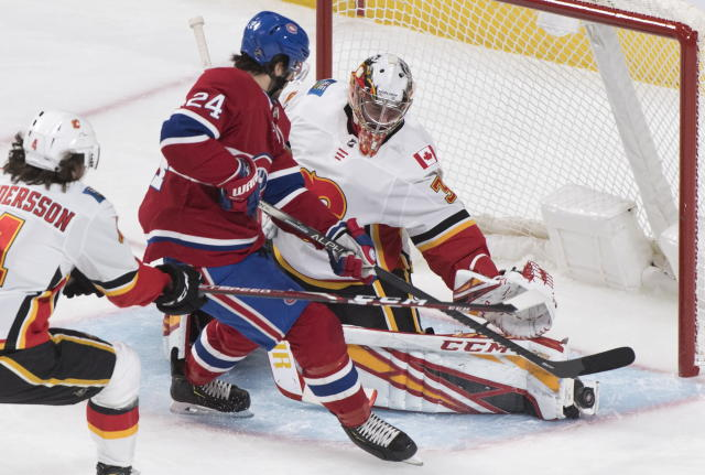 Montreal Canadiens' Phillip Danault (24) moves in on Calgary Flames goaltender David Rittich as Flames' Rasmus Andersson (4) defends during second period NHL hockey action in Montreal, Monday, Jan. 13, 2020. (Graham Hughes/The Canadian Press via AP)