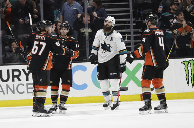 Anaheim Ducks' Rickard Rakell (67) celebrates his goal with teammates as San Jose Sharks' Brent Burns, second from right, skates past during the third period of an NHL hockey game Friday, March 22, 2019, in Anaheim, Calif. (AP Photo/Marcio Jose Sanchez)