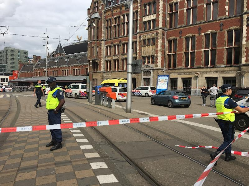 Security officials cordon off an area outside the Central Railway Station in Amsterdam following an attack by a knife-wielding man who wounded two American tourists