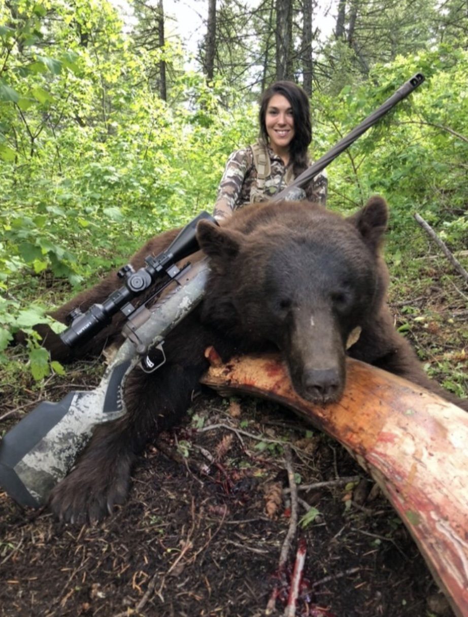 Kate Small is seen with a dead bear laying on a log and her rifle gun.