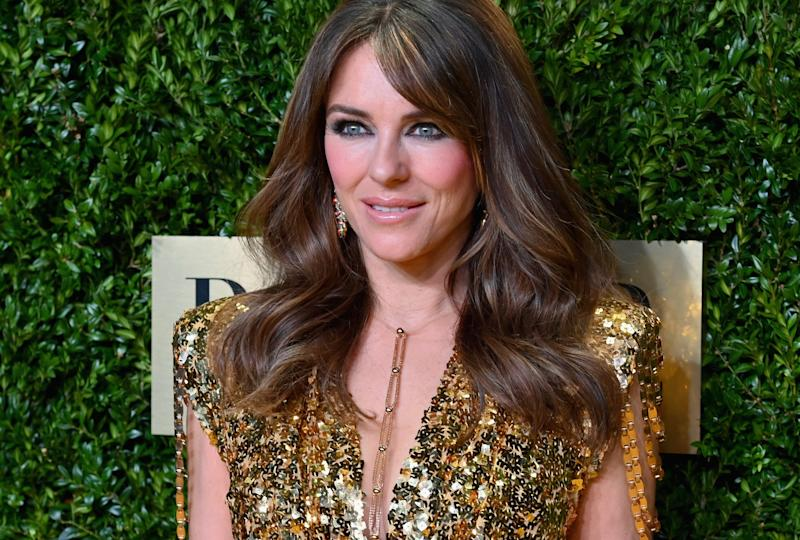 Elizabeth Hurley poses on the red carpet in gold dress