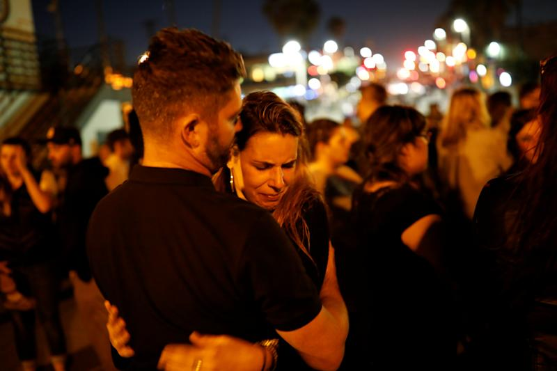 People embrace during a memorial for victims of the Oct. 1 Las Vegas Route 91 music festival mass shooting. (Patrick Fallon / Reuters)