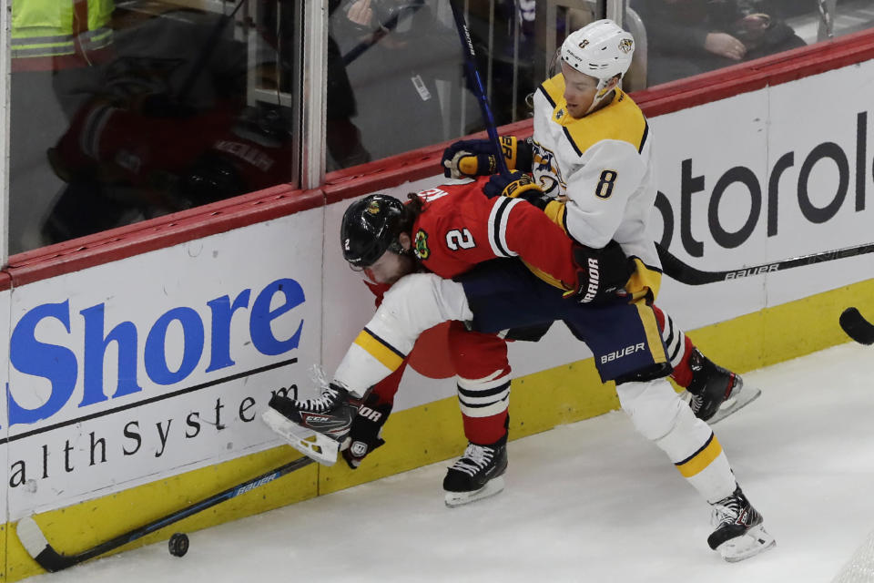 Chicago Blackhawks defenseman Duncan Keith, left, and Nashville Predators center Kyle Turris battle for the puck during the second period of an NHL hockey game in Chicago, Friday, Feb. 21, 2020. (AP Photo/Nam Y. Huh)