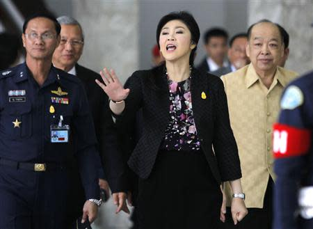 Thailand's Prime Minister Yingluck Shinawatra gestures as she leaves the Royal Thai Air Force Headquarters, after a cabinet meeting in Bangkok January 23, 2014. Thailand's Constitutional Court said it would decide on Thursday whether to accept a case against holding the February 2 election that would almost certainly extend the government's shaky grip on power as protesters try to force it from office. REUTERS/Chaiwat Subprasom