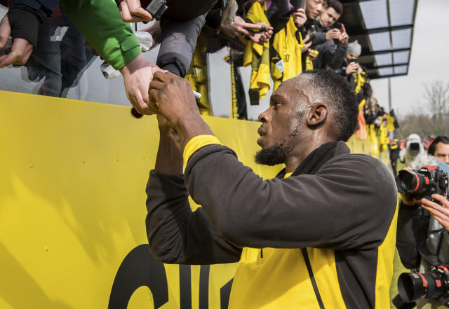 Jamaica's former sprinter Usain Bolt, signs autographs during a practice session of the Borussia Dortmund soccer squad in Dortmund, Germany, Friday, March 23, 2018. (Guido Kirchner/dpa via AP)
