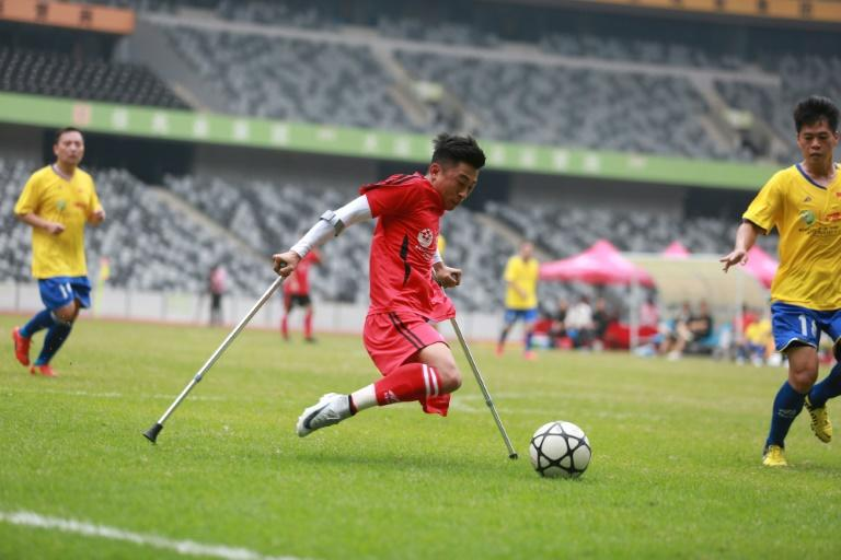 21-year-old He Yiyi lost his leg to childhood cancer and uses crutches to support himself when playing