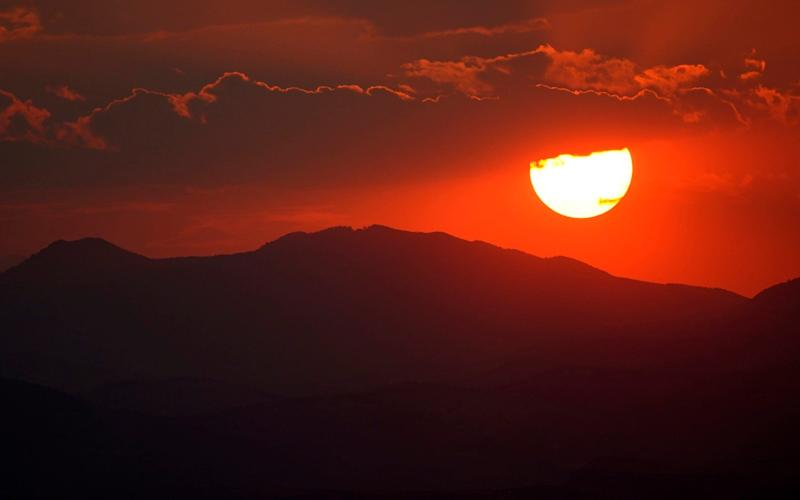 The sun sets behind the Rocky Mountains and turns the sky red as wildfires burn across the state of Colorado last month. Fires and high temperatures are thought to have disrupted the migration of thousands of birds - David Zalubowski /AP