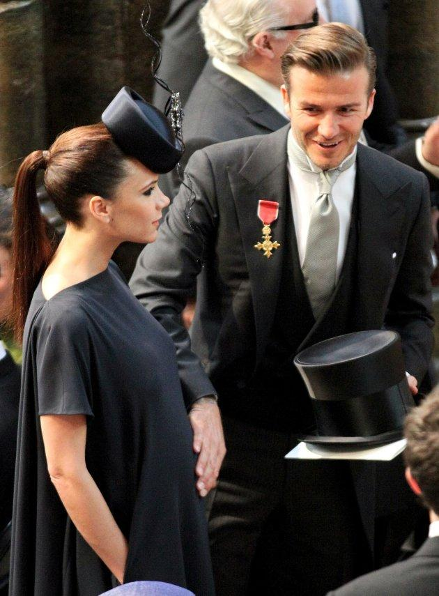 Football player David Beckham (R) puts his hand on the stomach of his pregnant wife Victoria as they take their seats for the Royal wedding of Prince William and Kate Middleton at Westminster Abbey in London April 29, 2011. REUTERS/Jon Bond/POOL (BRITAIN - Tags: SPORT SOCCER ROYALS ENTERTAINMENT PROFILE)