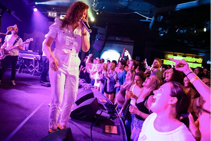 A singer in a white jumpsuit illuminated in purple sings on the edge of a stage above a crowd of people.