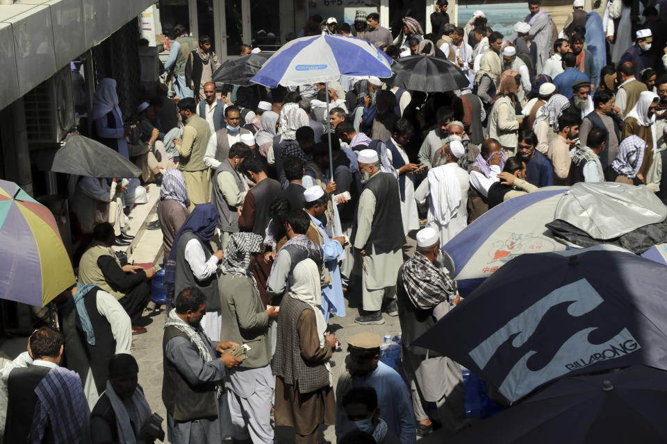 Afghan money changers wait for customers in the courtyard of the currency exchange Sarai Shahzada market in Kabul, Afghanistan, Saturday, Sept. 4, 2021. (AP Photo/Wali Sabawoon)
