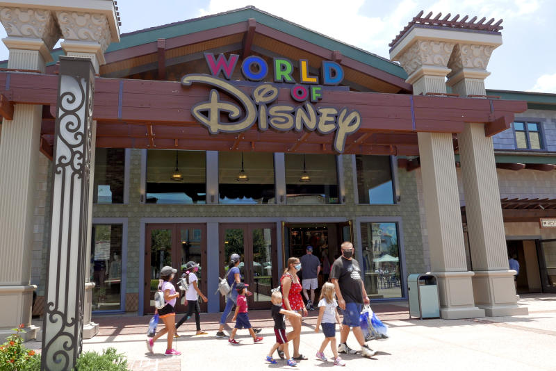Shoppers wearing masks because of the coronavirus pandemic stroll by the World of Disney store at the Disney Springs shopping, dining and entertainment complex Tuesday, June 16, 2020, in Lake Buena Vista, Fla. Walt Disney World Resort theme parks plan to reopen on July 11. (AP Photo/John Raoux)