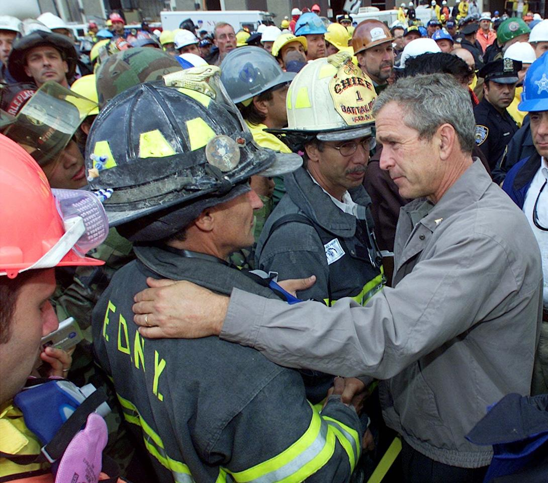 As rescue efforts continue in the rubble of the World Trade Center, President Bush greets firefighters at the site during a tour of the devastation, Friday, September 14, 2001. Bush is standing on a burned fire truck. Bush toured the disaster site on foot after getting a helicopter view of the devastation. (AP Photo/Doug Mills)