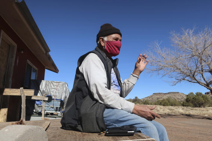 Raymond Clark sits outside his home in Teesto, Ariz., on the Navajo Nation on Thursday, Feb. 11, 2021. Teesto workers, health representatives, volunteers and neighbors keep close tabs on another to ensure the most vulnerable citizens get the help they need. (AP Photo/Felicia Fonseca)