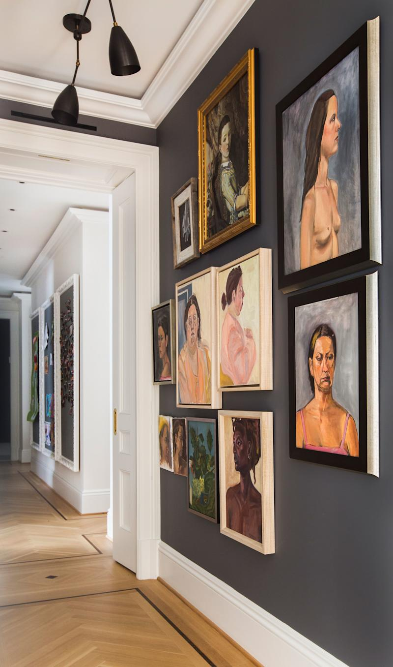 """To decorate the hallways of the apartment, Grehl took a cue from Frank Lloyd Wright's concept of compression and release. """"The idea was to create a dark central section and then an explosion of light in the periphery,"""" she says. All of the portraits on this wall were painted by homeowner Claire Wolinsky, who studied fine arts before becoming a doctor. The custom-installed """"Twig"""" ceiling pendants are from Apparatus."""