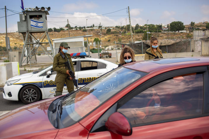 """FILE - In this Tuesday, June 30, 2020 file photo, Israeli soldiers check the ID of a Palestinian woman at the Tapuach junction checkpoint next to the West Bank city of Nablus. Israel's premier human rights group has begun describing both Israel and its control of the Palestinian territories as a single """"apartheid"""" regime, using an explosive term that the Israeli government and its supporters vehemently reject. (AP Photo/Oded Balilty, File)"""