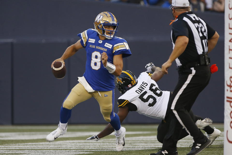 Winnipeg Blue Bombers quarterback Zach Collaros (8) gets away from Hamilton Tiger-Cats defensive end Ja'Gared Davis (56) during the first half of a Canadian Football League game Thursday, Aug. 5, 2021, in Winnipeg, Manitoba. (John Woods/The Canadian Press via AP)