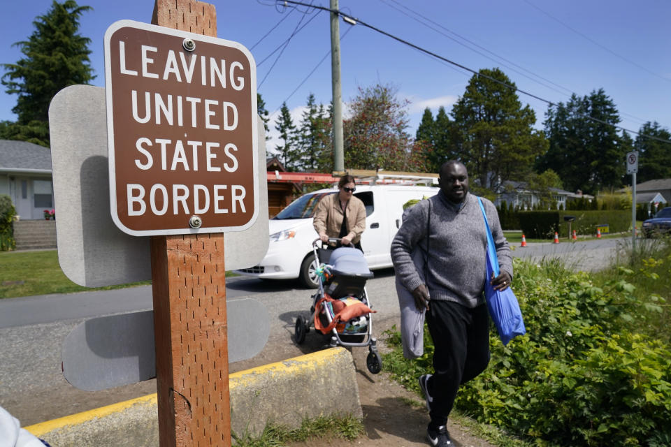 Canadian residents Philip Owira, right, and Katherine Nichol walk with their baby across a small ditch from Canada into Peace Arch Historical State Park to visit a friend there, Tuesday, June 8, 2021, in Blaine, Wash. The border has been closed to nonessential travel since March 2020, but Canadians have been allowed to walk over the ditch into the U.S. park. (AP Photo/Elaine Thompson)
