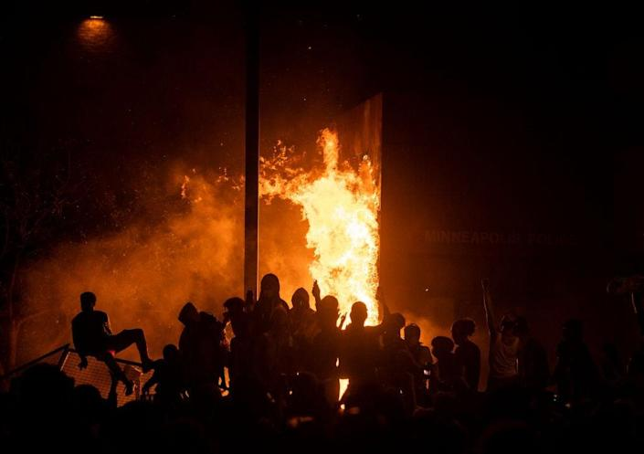 Protesters cheer as the Third Police Precinct burns behind them on May 28, 2020, in Minneapolis, Minnesota. As unrest continues after the death of George Floyd police abandoned the precinct building, allowing protesters to set fire to it. (Photo by Stephen Maturen/Getty Images)