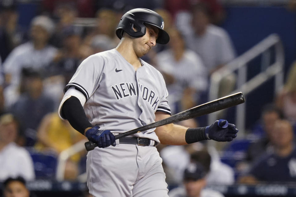 New York Yankees' Joey Gallo looks at his bat after striking out during the first inning of the team's baseball game against the Miami Marlins, Friday, July 30, 2021, in Miami. (AP Photo/Lynne Sladky)