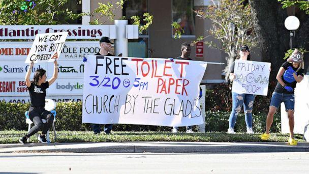 PHOTO: People offer free toilet paper in Coral Springs, Fla., Mar 19, 2020. (Larry Marano/REX)