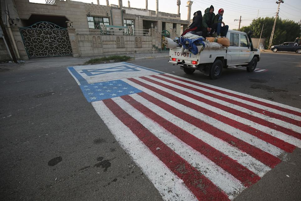 A mock US flag is painted on the ground for cars to drive on in the Iraqi capital Baghdad on January 3, 2020, following news of the killing of Iranian Revolutionary Guards top commander Qasem Soleimani in a US strike on his convoy at Baghdad international airport. (Photo by AHMAD AL-RUBAYE / AFP) (Photo by AHMAD AL-RUBAYE/AFP via Getty Images)