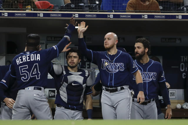 Tampa Bay Rays' Guillermo Heredia (54) is greeted by teammates after scoring off a fly ball by Jesus Aguilar during the seventh inning of a baseball game against the San Diego Padres Monday, Aug. 12, 2019, in San Diego. (AP Photo/Gregory Bull)